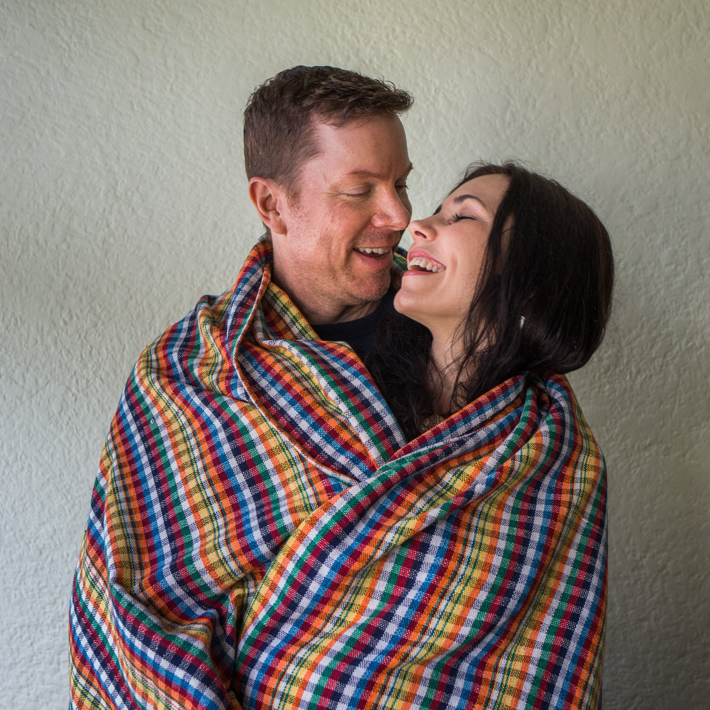 happy couple wrapped in blanket