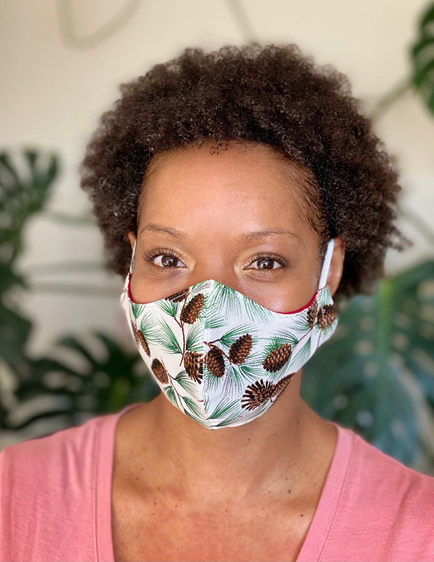 Woman wearing holiday face mask with pine cones