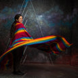 woman wraped in rainbow blanket pink floyd dark side of the moon