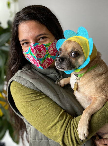 woman and dog wearing floral face mask dog dressed like a flower