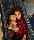 child in hammock with teddy bear