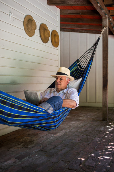 older white man reading in hammock