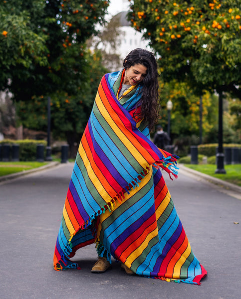 woman wrapped on cotton rainbow blanket by Maria Canta