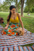 woman in floral wrap skirt at the park with dog