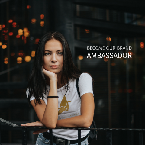 Become our Brand Ambassador - A woman leaning over a railing in our logo shirt looking stunning.