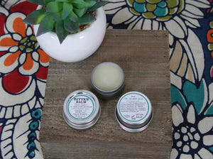 Bitten balm product, lid, and base showing ingredients