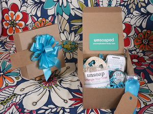 gift box including unsoap butter scrub bar with pink himalayan salt exfoliant, loofah to set unsoap on, calm balm, and unlotion solid lotion bar, with gift tag and pull bow