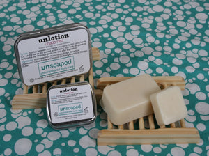 unlotion solid lotion bars in both small 0.6 ounce and large 2 ounce sizes with labeled metal hinged tins