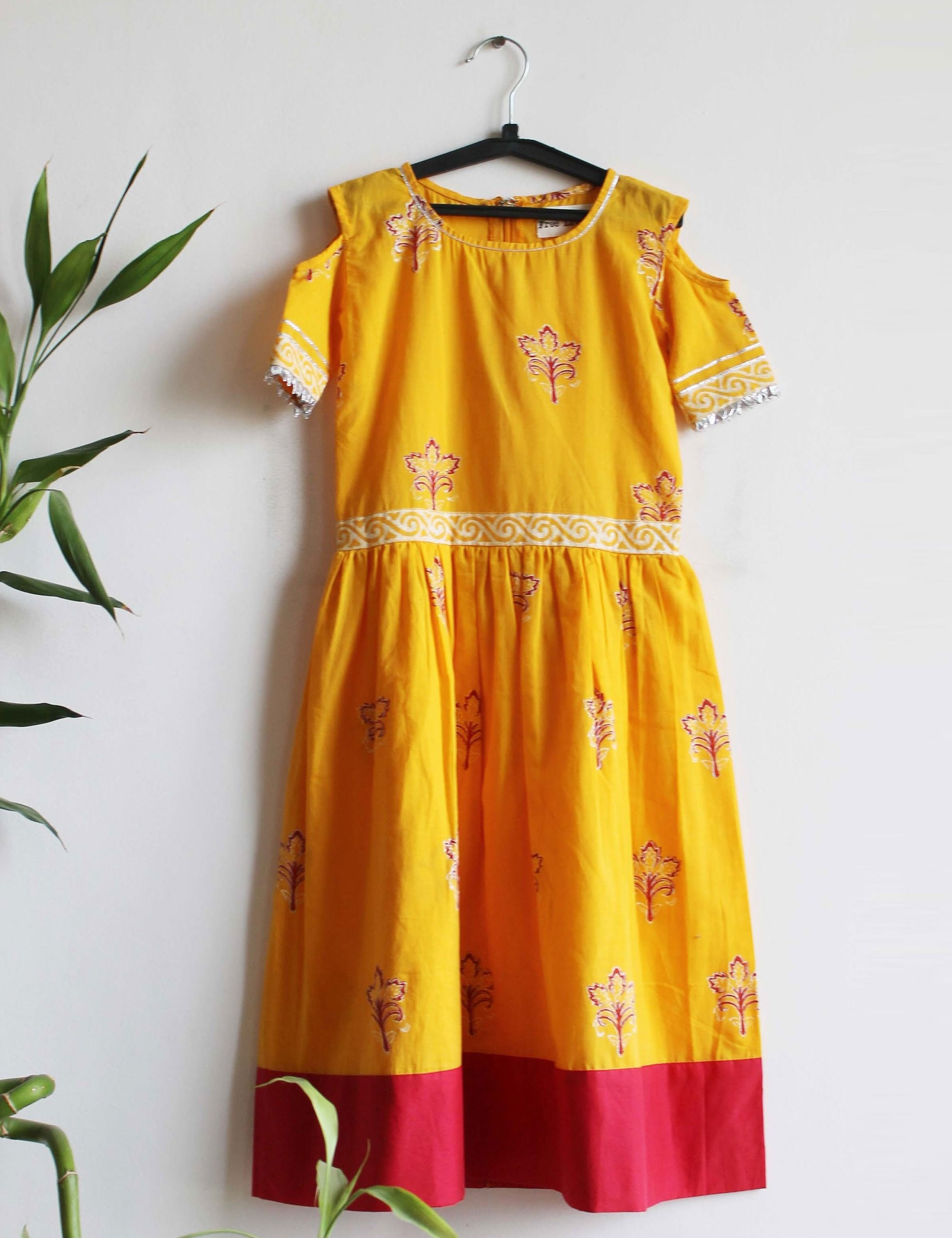 A Cold Shoulder Dress in Yellow Colour with A Red Border for Girls