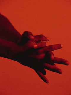 hands clasping together against red background