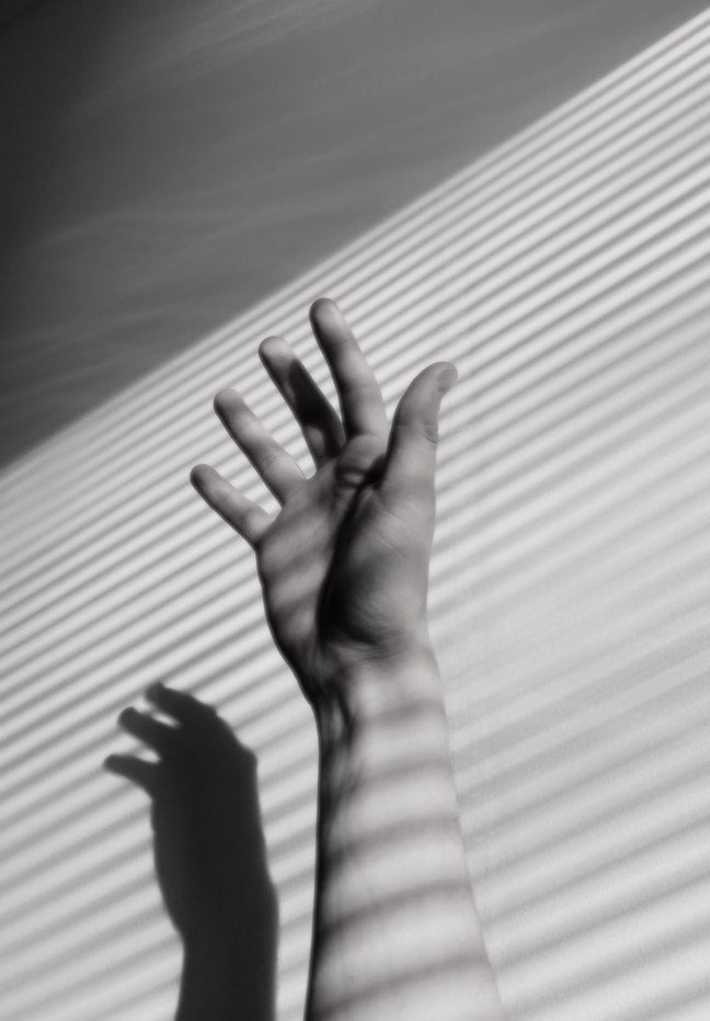 black and white hand with rays of sun against wall