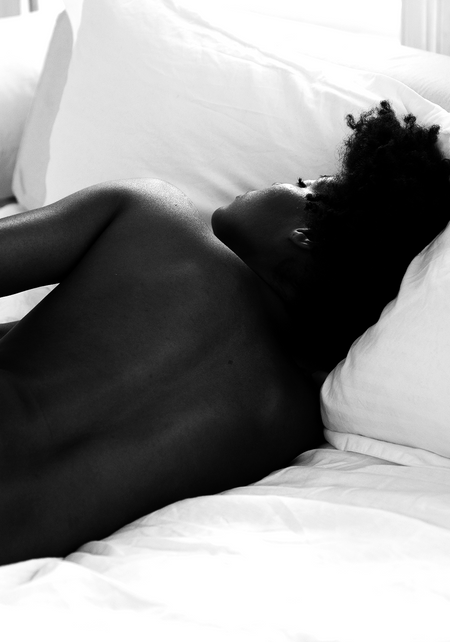 african american woman laying down in bed