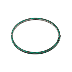 A bangle set on three sides with brilliant cut emeralds in blackened 18 karat white gold by Solange Azagury-Partridge