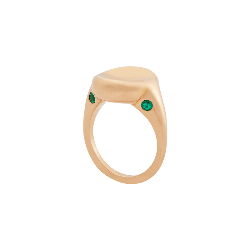 A ring with a round concave top set with two emeralds on the front and back in 18 karat yellow gold ring y Solange Azagury-Partridge