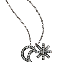 A moon and star motif pendant set with brilliant cut diamonds in blackened 18 karat white gold by Solange Azagury-Partridge