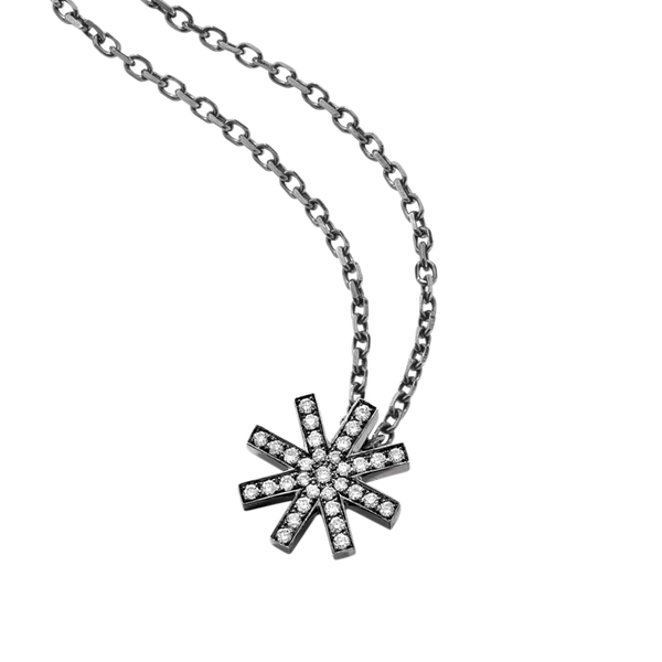 A delicate star motif pendant set with brilliant cut diamonds with a long chain in blackened 18 karat white gold by Solange Azagury-Partridge