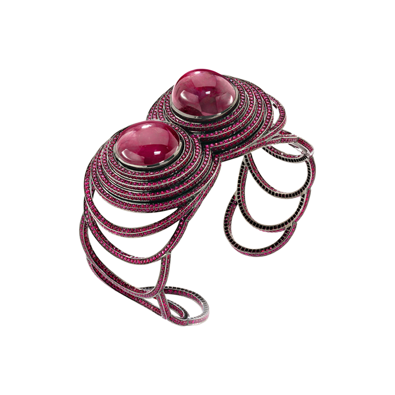An open  work cuff composed of twin star and cabochon rubies with rubies pavé surrounded set in blackened 18 karat white gold by Solange Azagury-Partridge