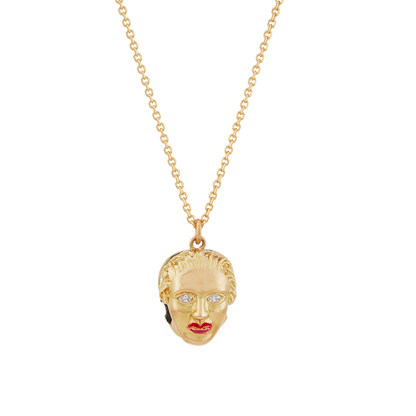 A pendant that respects the inevitability of death, half skull and half human face with diamond eyes and ruby red lacquered lips set in 18 karat yellow gold pendant on a chain by Solange Azagury-Partridge