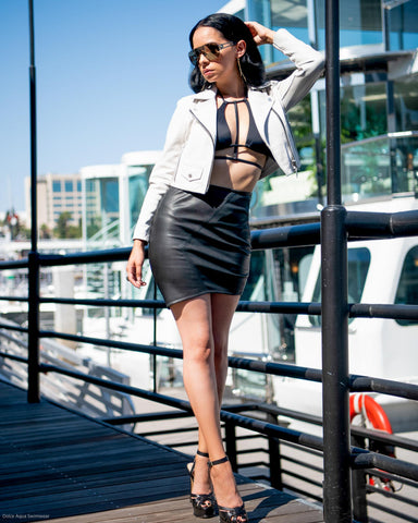 Black halter harness bikini top with leather skirt and cropped jacket