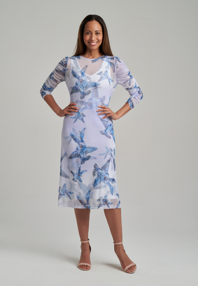 Woman wearing mesh three quarter sleeve dress over stretch knit short dress with blue birds printed
