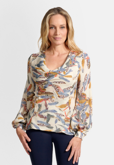 Model wearing cream cowl neck silk blouse top printed with feathers