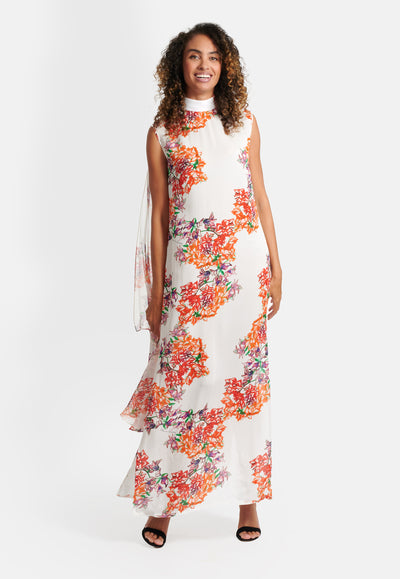 Model wearing silk orange and white flower printed long sleeveless dress with mesh shoulder shawl attached to the high neck collar