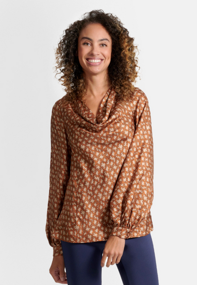Model wearing geometric brown bird patter cowl neck silk blouse top