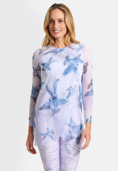 Model wearing long sleeve mesh crew neck lavender top with blue birds printed on it