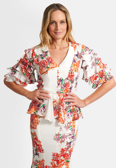 Model wearing silk orange and white flower printed peplum top with buttons and ruffled sleeves