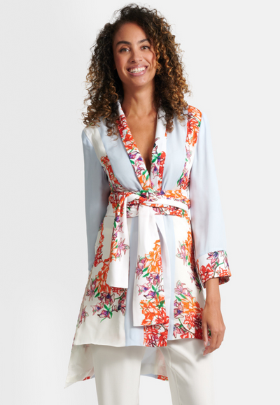 Model wearing silk blue paneled orange and white flower printed kimono style jacket with orange and white flower printed belt