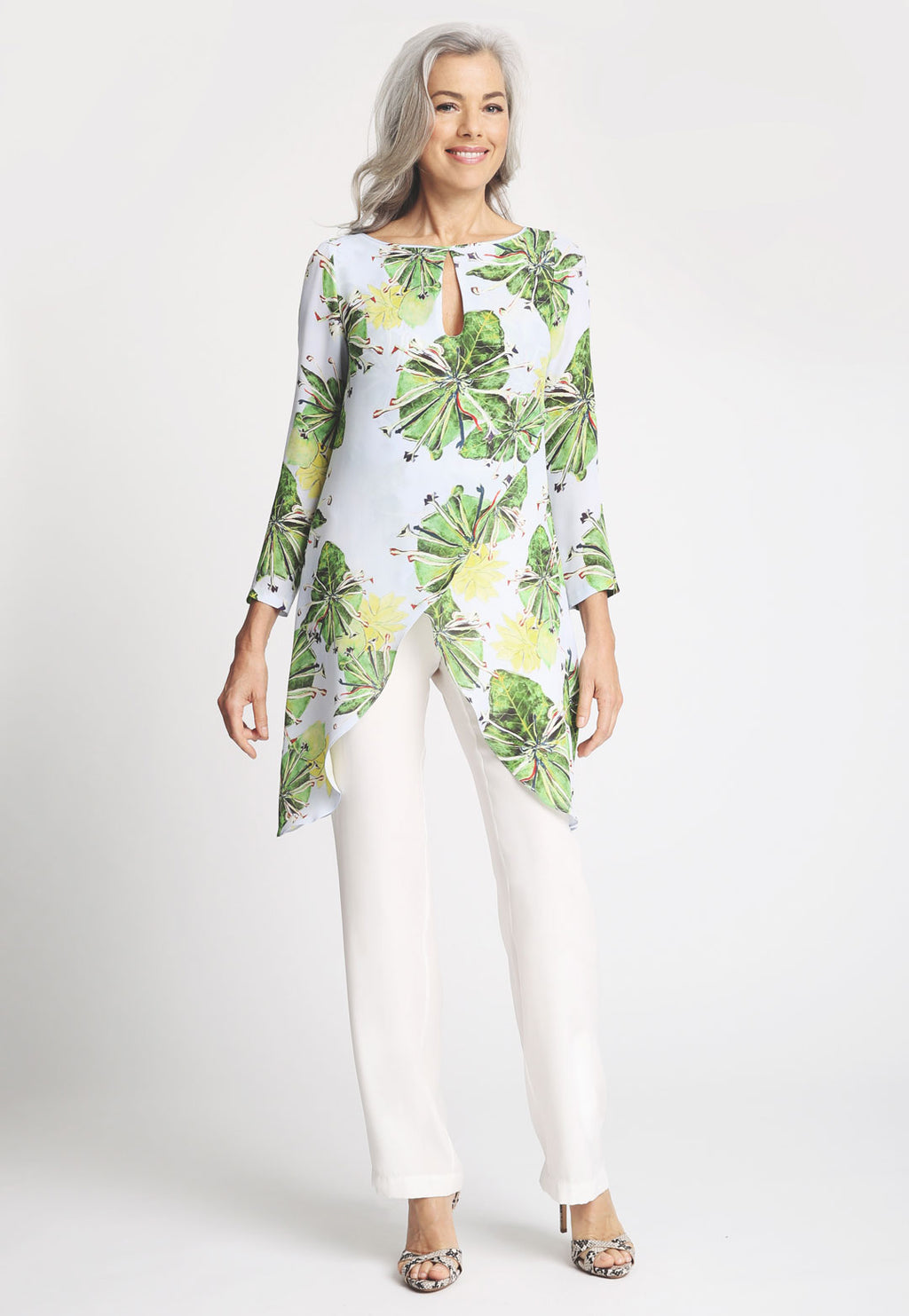Model in asymmetrical three quarter sleeve blouse with a keyhole and white pant