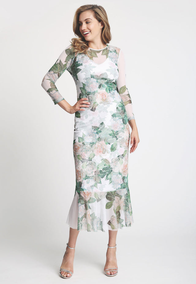 Model in three quarter length sleeve gardenia printed dress with ruffle bottom
