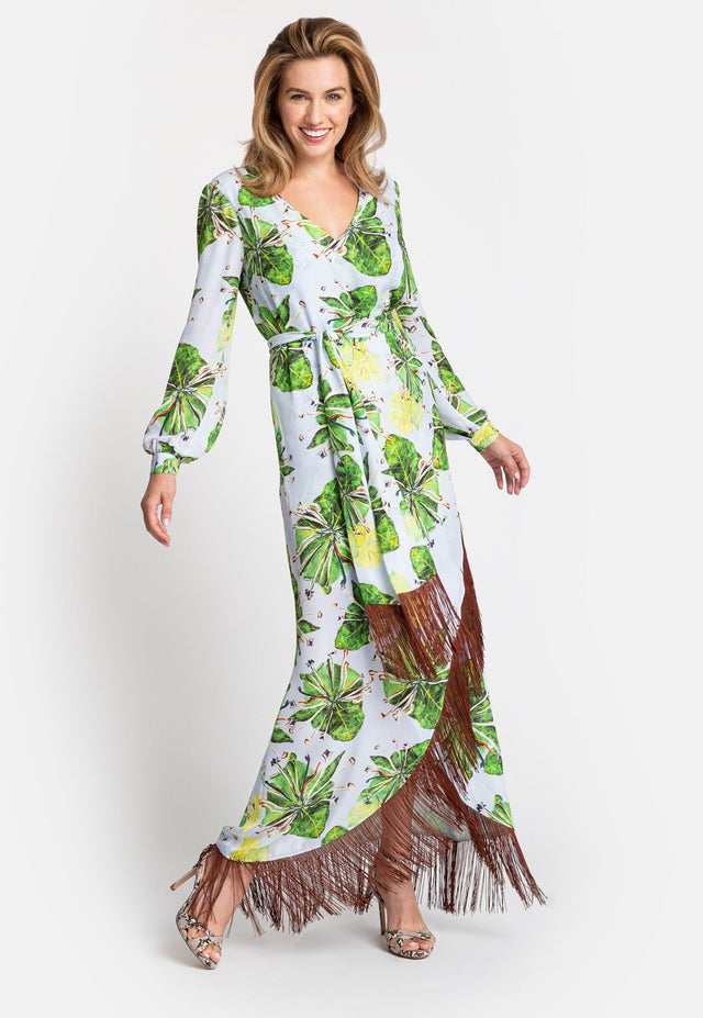 Model in long sleeve green floral printed wrap dress with brown fringe along the bottom edge