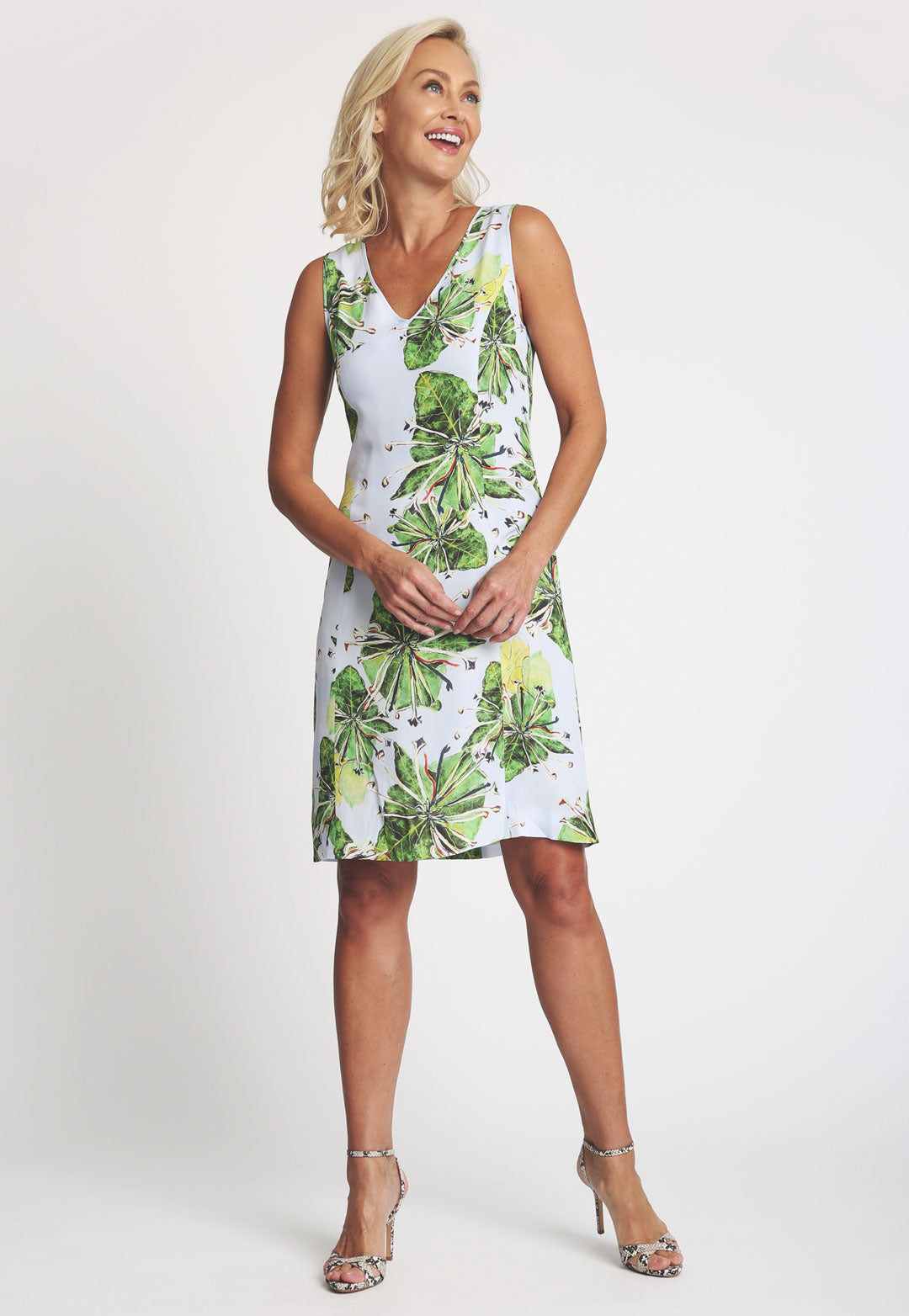 Model in knee length green floral printed sleeveless dress