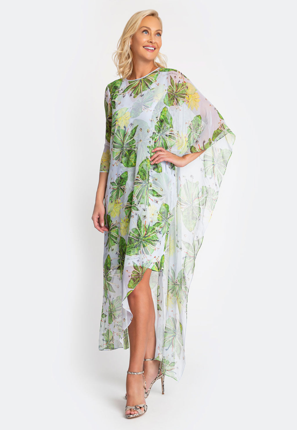Model in green asymmetrical printed poncho with one three quarter length sleeve