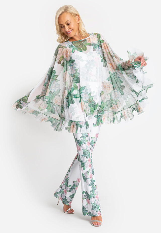 Model in gardenia printed poncho with ruffles on the bottom and a matching pant