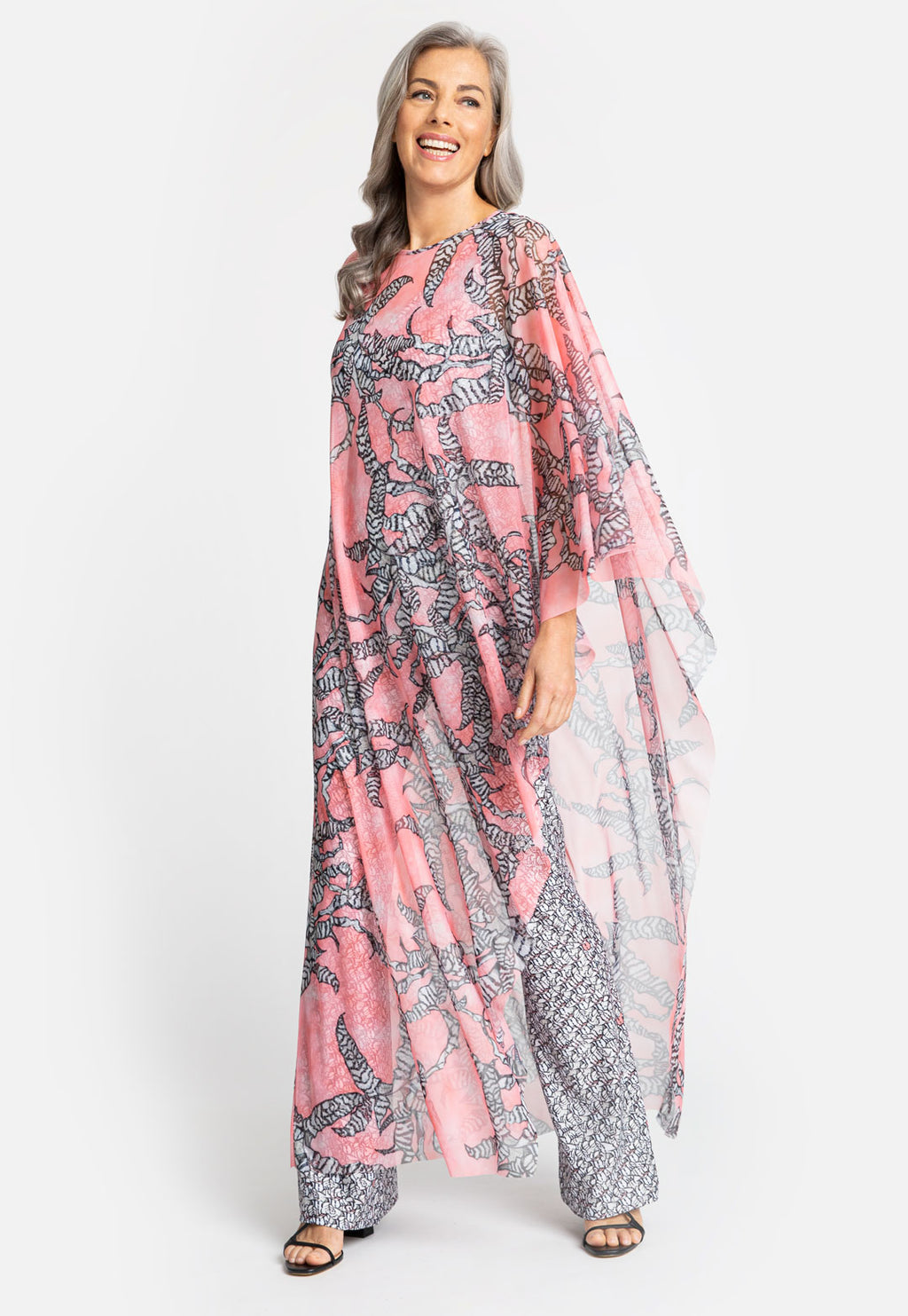 Model in long pink printed poncho with one sleeve and black and white printed dress underneath