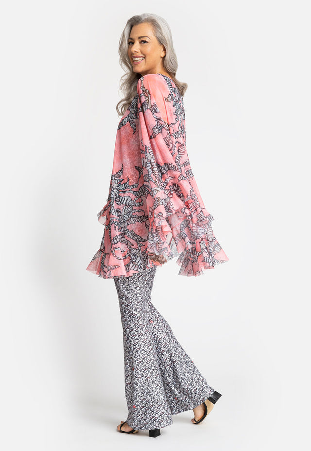 Model in pink poncho with black and white floral print
