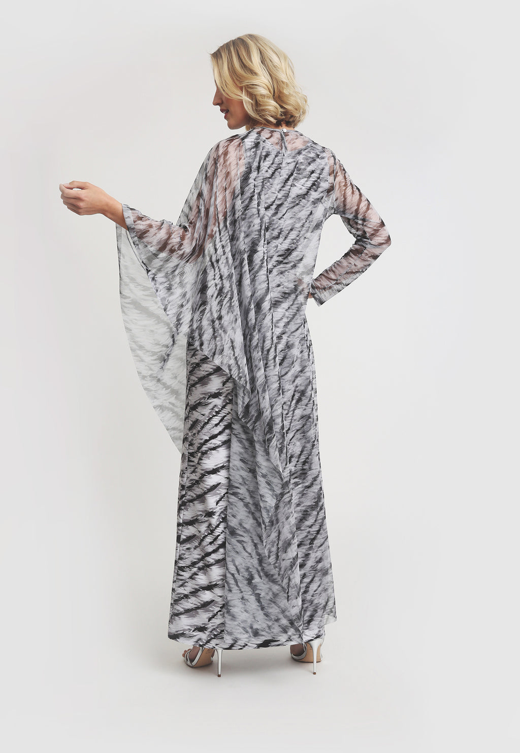 Model in long mesh black and white tiger print poncho with one sleeve with matching dress underneath