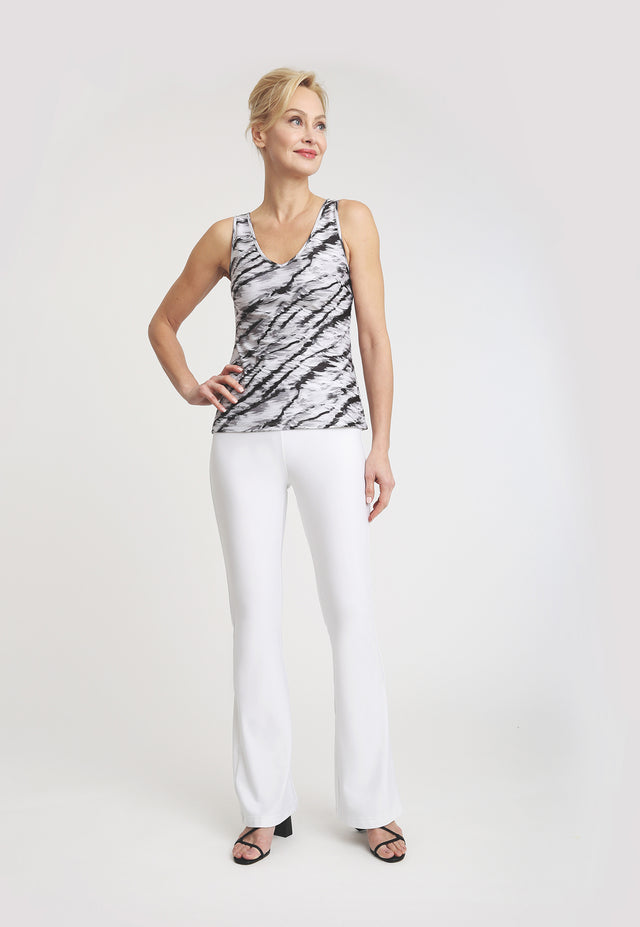 Model wearing black and white tank top with white pants