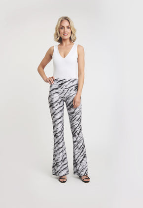 Model in a black and white tiger print pant with white tank top