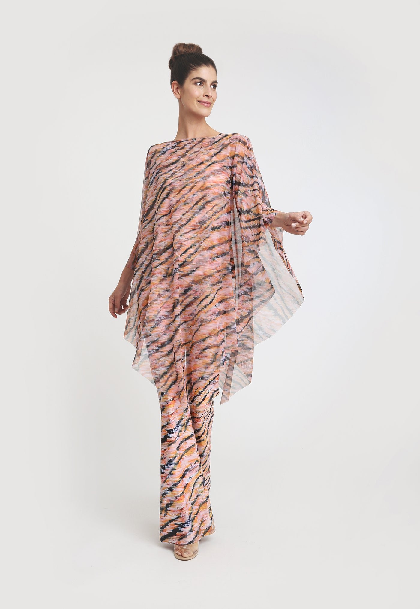 Model in triangle cut mesh poncho with pink and black tiger print, over matching tank top and pant