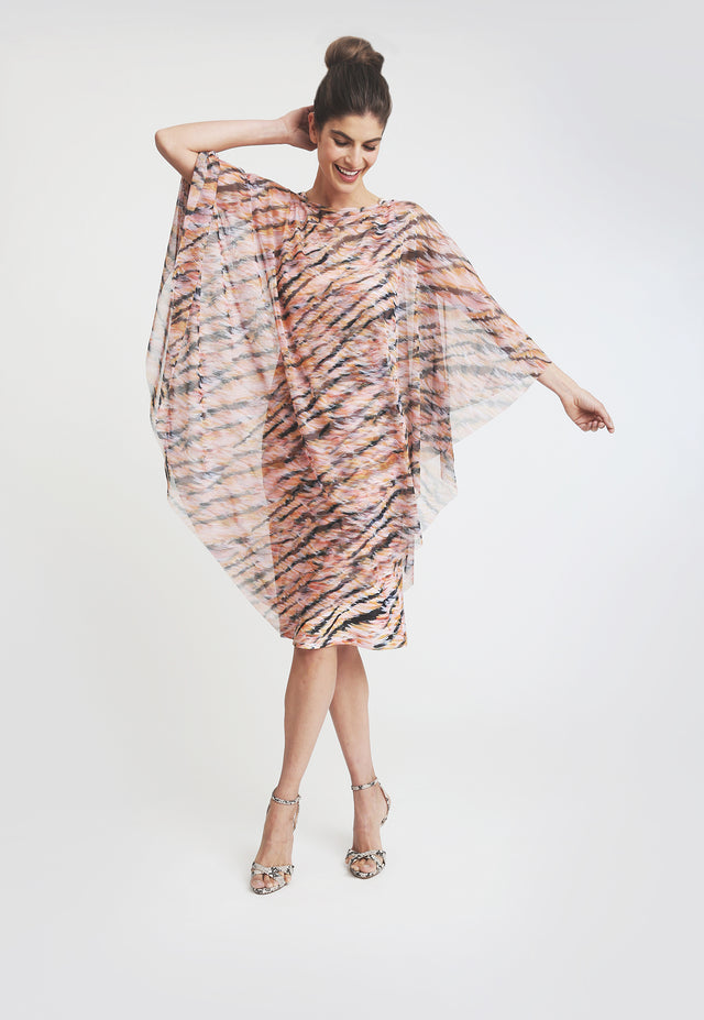 Model in triangle cut mesh poncho with pink and black tiger print, over matching knee length dress