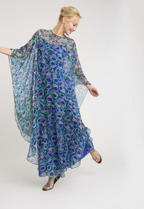 Model in long blue slip dress with long sheer poncho with a peacock print