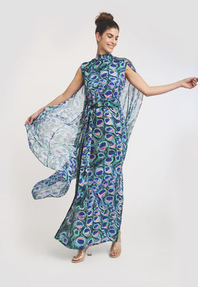 Model in long peacock printed dress and mandarin collar with sheer printed shall on both shoulders