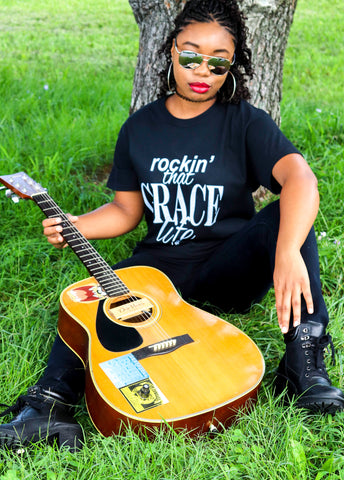 Girl with Rockin' that Grace Life tee on in black and white sitting on gras with a guitar