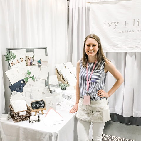 Brenna, Owner and Designer of Ivy + Linen Design Co., standing in her booth at Girl Tribe Charlotte 2019