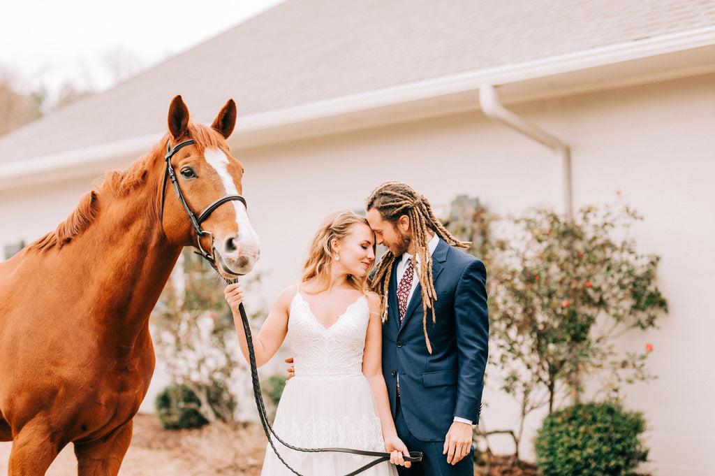 Bride and Groom with a beautiful horse at the styled shoot at Old Homestead Farm in Rocky Point, NC. Photo by Chelsea Allegra Photography.