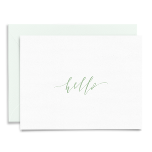 Calligraphy and hand lettered Hello folded greeting card on linen cardstock with green font and a coordinating light green envelope
