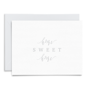 Calligraphy and hand lettered Home Sweet Home folded greeting card on linen cardstock with gray font and a coordinating light gray envelope to match